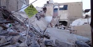 """Flugblätter der Kampagne in einer zerstörten Nachbarschaft von Homs. Dieses besagt: """"13 Nachbarschaften seit dem 9. Juni 2012 unter Belagerung"""". Quelle: Facebook-Seite der Kampagne."""