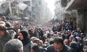 BewohnerInnen von Yarmouk stehen im Februar 2014 an, um von der  Lebensmittelhilfe des Roten Halbmonds zu profitieren.