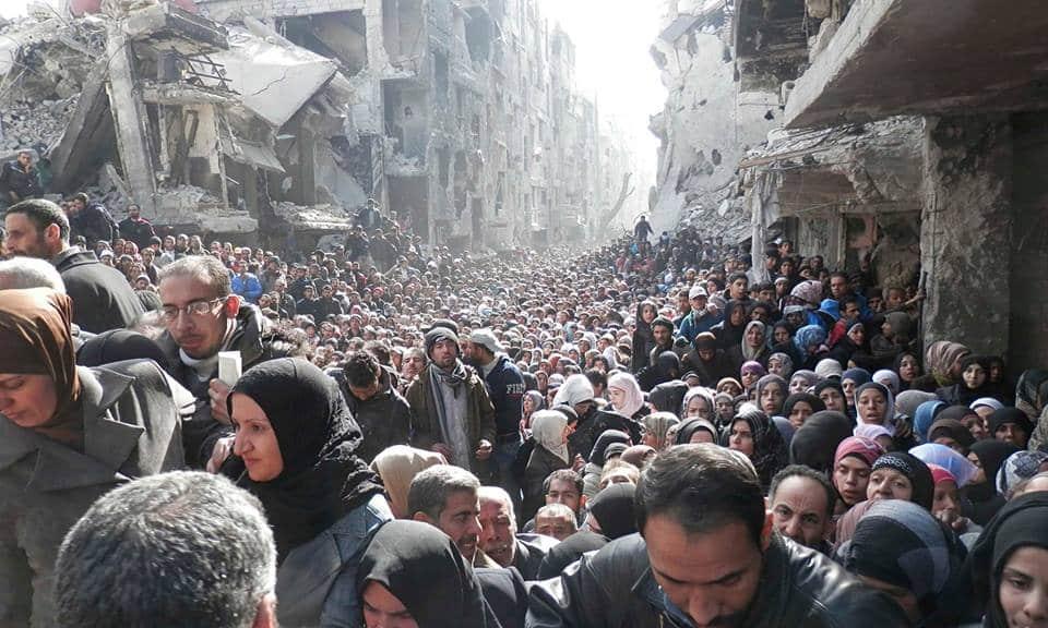BewohnerInnen von Yarmouk stehen im Februar 2014 für Hilfsgüter des Roten Halbmonds an