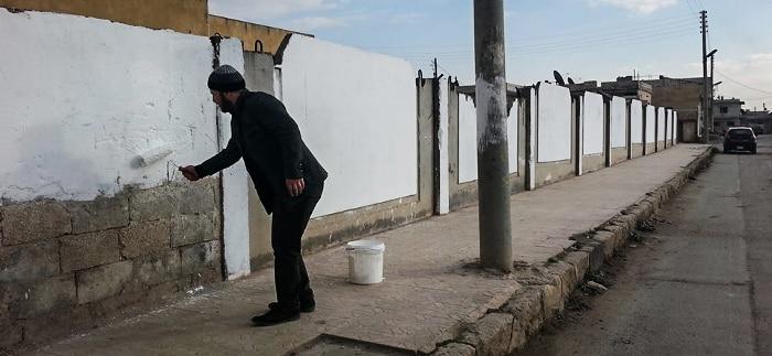AktivistInnen entfernen in Atareb die Parolen radikalislamistischer Kämpfer
