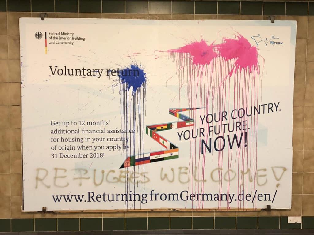 Cartel grafiteado en una estación de metro en Berlín